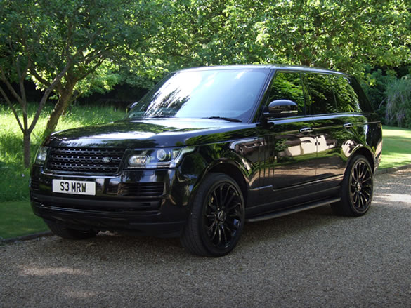An image of a black Range Rover Vogue SE taken in a gravel driveway surrounded by trees.