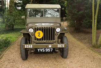 An image of a dark green Army Willys Jeep taken in a gravel driveway surrounded by trees.